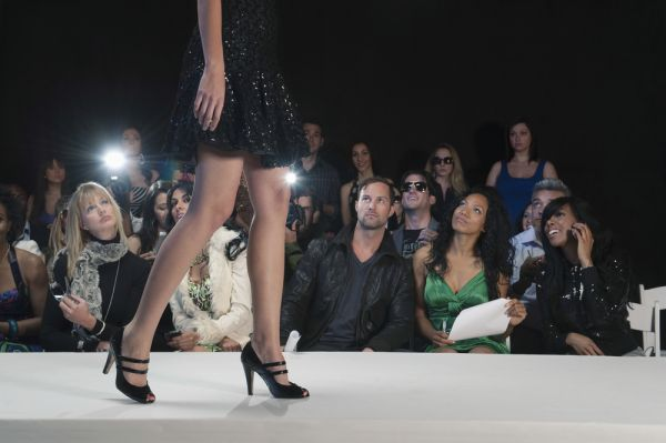 Fashion show runway with onlookers and model in heels
