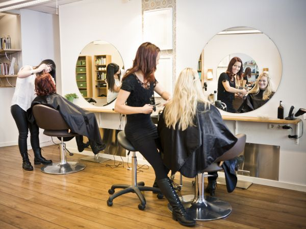 Beauty salon image with clients in hair with smiling cosmetologists